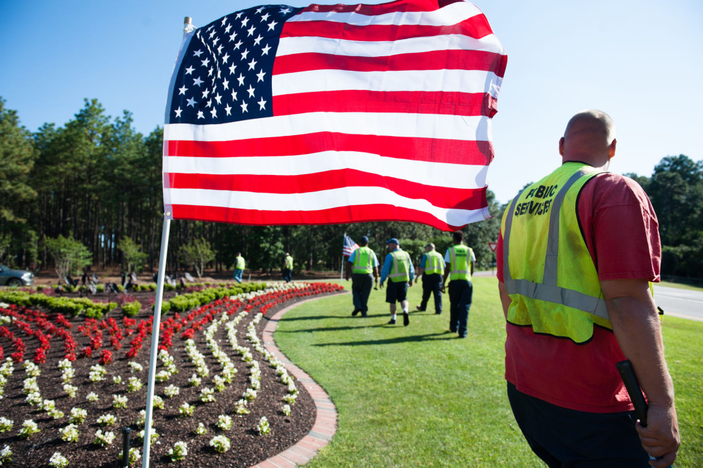 Public Service worker J.C. Clark (right) works with others as they post flags at the triangles off the large traffic circle on Friday, May 22, 2015 in Pinehurst, North Carolina. The workers posted flags down Midland Road, all triangles of the large traffic circle, a smaller circle near Pinehurst Resort and Marshall Park, totaling 125 American Flags for the Memorial Holiday weekend.