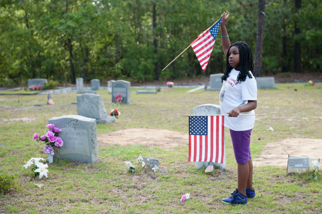 Eight-year-old Amauri Chalmners of Southern Pines points to veterans graves at the Woodlawn Cemetery on Friday, May 22, 2015 in Southern Pines, North Carolina.