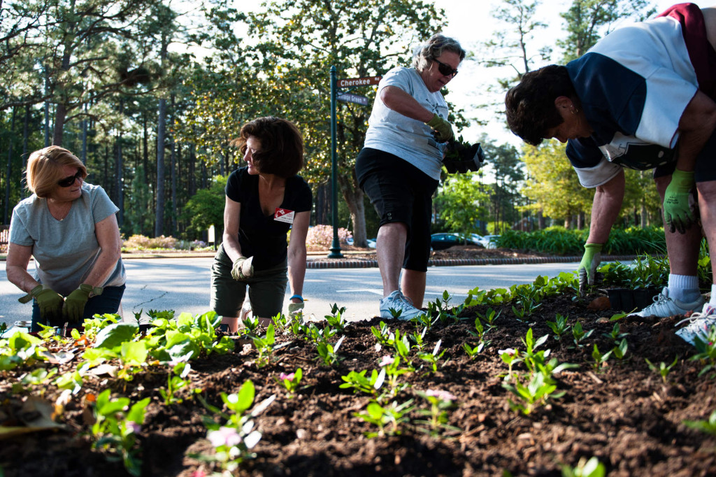 Lois Prchlik (far left) and master gardener volunteer Victoria Flaherty (center) chat as they, along with fellow Dogwood Branch members of the Pinehurst Garden Club, plant in flowerbeds during Spring Planting Day near the flagpole on Tuesday, May 5, 2015 in downtown Pinehurst, North Carolina. The group planted mixed vincas throughout the square.