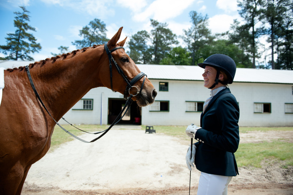 Lisa Wall, of Apex, laughs as she stands with her horse Baaron Miller Rh outside of barn 11, after riding at their scheduled time, during the Dressage in the Sandhills Horse Show at the Pinehurst Harness Track on Friday, May 8, 2015 in Pinehurst, North Carolina.