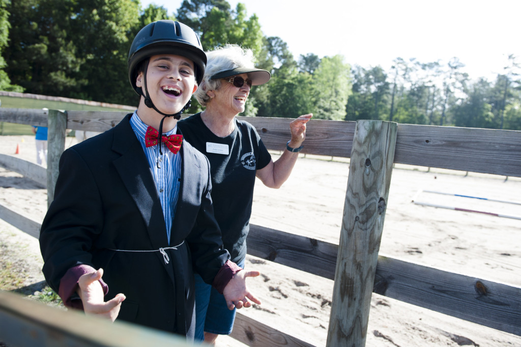 Nicki F. smiles while Judy Lewis (center, background) laughs as he waits to get on his horse to compete during a Prancing Horse show at Muddy Creek Farm off Trails End Road on Monday, May 11, 2015 in Whispering Pines, North Carolina.
