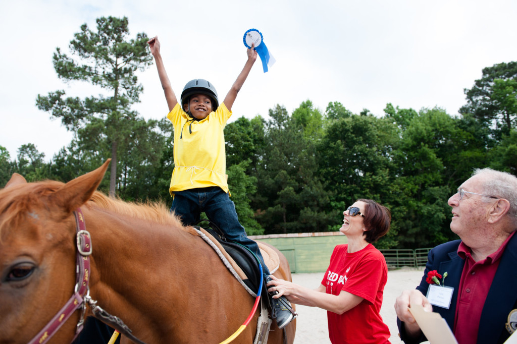 Volunteer Claire Slyman laughs as 6-year-old Daryl Green smiles and celebrates his ribbon after placing during a Prancing Horse show at Muddy Creek Farm off Trails End Road on Thursday, May 14, 2015 in Whispering Pines, North Carolina.