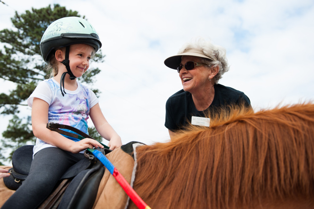 Five-year-old Emmylyn Justin smiles to Judy Lewis after she got on Funny all by herself during a Prancing Horse show at Muddy Creek Farm off Trails End Road on Thursday, May 14, 2015 in Whispering Pines, North Carolina.