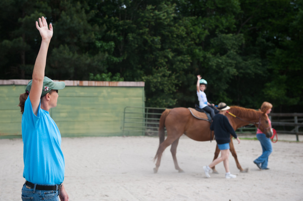Certified therapeutic riding instructor Susan Price stretches her right arm, asking her riders to do the same, during a Prancing Horse show at Muddy Creek Farm off Trails End Road on Thursday, May 14, 2015 in Whispering Pines, North Carolina.