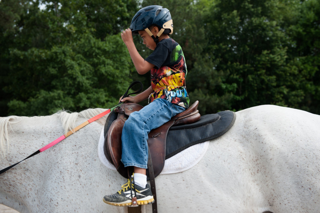 Seven-year-old Elijah Grady straightens the rim of his riding helmet during a Prancing Horse show at Muddy Creek Farm off Trails End Road on Thursday, May 14, 2015 in Whispering Pines, North Carolina.