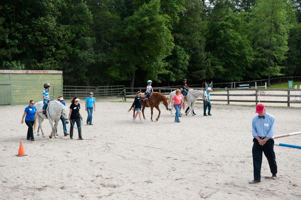 Show judge Bill Lewis (far right) walks to the rail so he can watch the group's riding pattern during a Prancing Horse show at Muddy Creek Farm off Trails End Road on Thursday, May 14, 2015 in Whispering Pines, North Carolina.