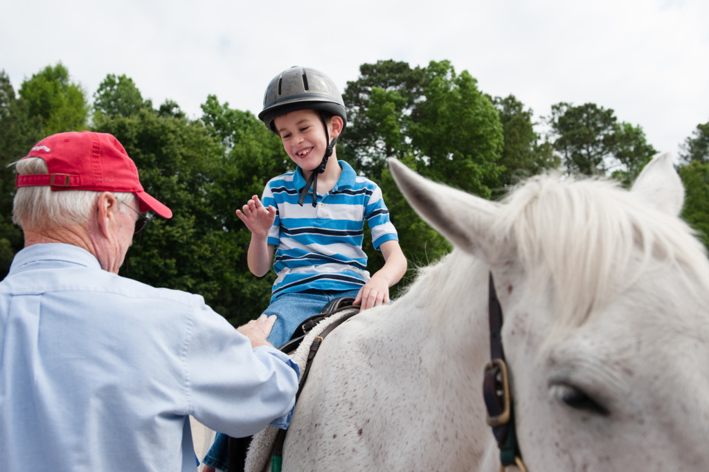 Nine-year-old Joseph Strobel smiles with show judge Bill Lewis (left) as he receives his awards after placing during a Prancing Horse show at Muddy Creek Farm off Trails End Road on Thursday, May 14, 2015 in Whispering Pines, North Carolina.