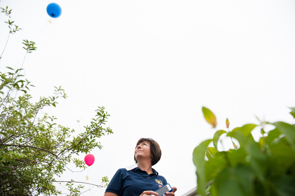 Principal Robin Calcutt watches balloons float away after students released them at West Pine Middle School for a garden dedication ceremony in honor of Mindi Zumwalt who recently lost her fight with cancer, on Friday, June 5, 2015 in Pinehurst, North Carolina.