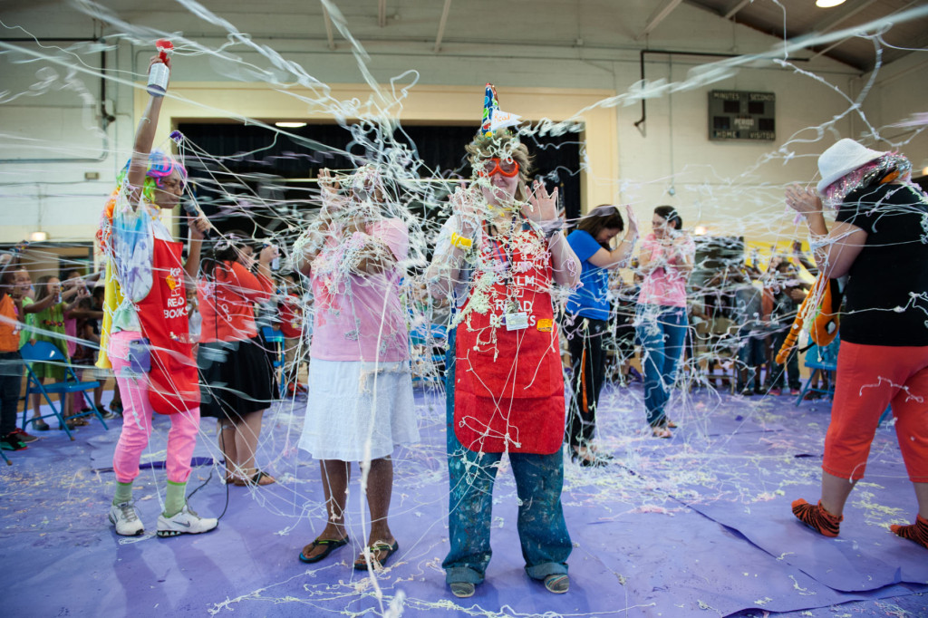 "Counselor Michelle Crews (center) stands with other teachers as students from the second grade class shoot silly string at them before ""shopping"" for their books at Aberdeen Primary School on Wednesday, June 10, 2015 in Aberdeen, North Carolina. Originally, as part of the ""Give 5, read 5"" book program, each student was allowed to choose 5 books among the donated books, but after the school collected 10,000 books, the students were able to pick out 25 books each."