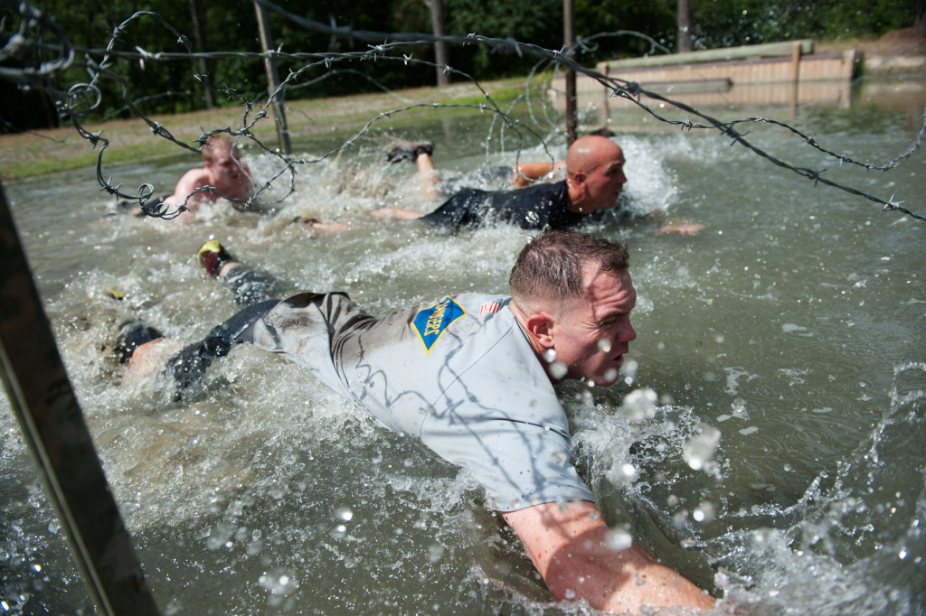 Teams in the wave of the competitors Muddy Nick 10K crawl through a water hazard, under lines of barbed-wire, during the Special Operators Challenge at the Carolina Horse Park on Saturday, May 30, 2015 in Raeford, North Carolina.