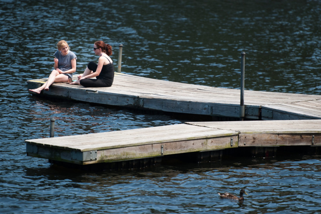 Rachel Whilden (left) and Rachael Davis (center) sit and chat on the dock at Reservoir Park on Tuesday, June 30, 2015 in Southern Pines. Whilden and Davis work together at Bonefish Grill and spend their free time at the park.