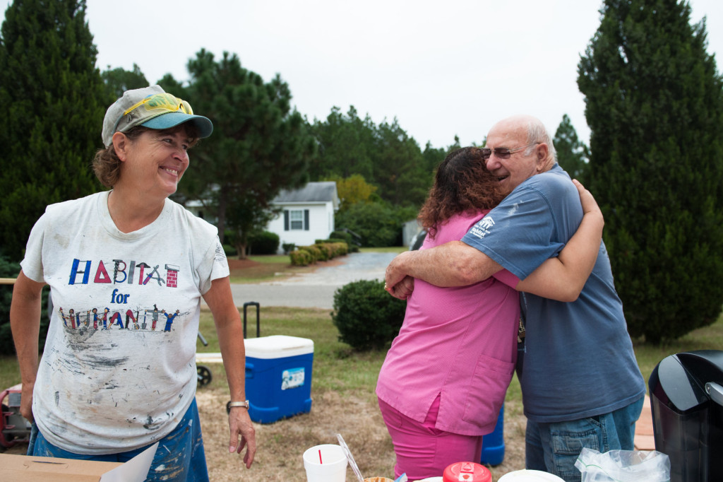 Soon-to-be Homeowner Roberta Blue hugs team wrangler and organizer Jack Paterek -- who works with the group volunteering their time-- as Stephanie Gray (left) smiles at a Habitat for Humanity site off Fuller's way on Tuesday, September 22, 2015 in Aberdeen, North Carolina.