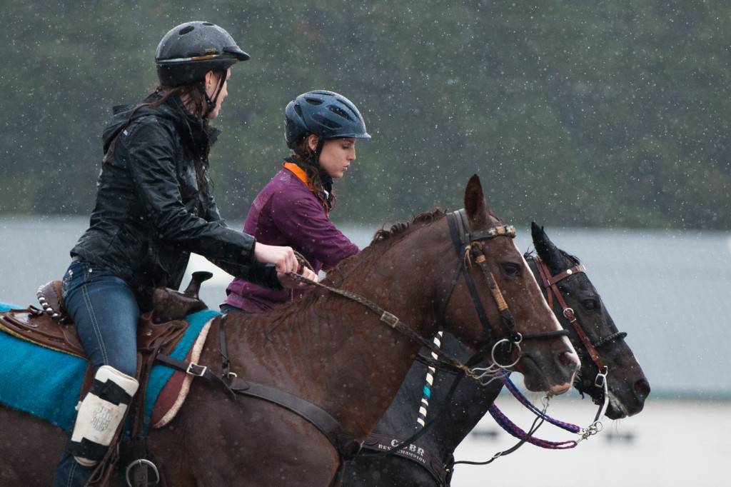 Fifteen-year-old Hannah Johnson rides Cami with 13-year-old Faith Kane (background) on Ebony as they work around barrels in the rain for practice on Saturday, October 10, 2015 at the Harness Track and Fair Barn in Pinehurst, North Carolina. The girls with the Central Carolina Barrel Racers were going to perform demonstrations for the Annie Oakley Boom Day event, but with the rain keeping most spectators away, the group decided to practice for the State Fair.