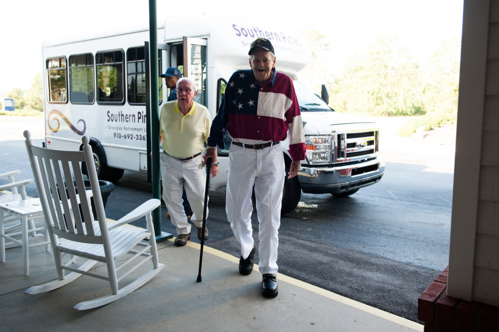 Adrian de Pasquale (center) and Harry Diebold (left) step off the bus to the entrance at the Moore County Airport to attend the Ageless Aviation event where  members of the Southern Pines Gracious Retirement Living Community will take turns riding in Darryl Fisher's Boeing Stearman on Tuesday, September 1, 2015 in Whispering Pines.