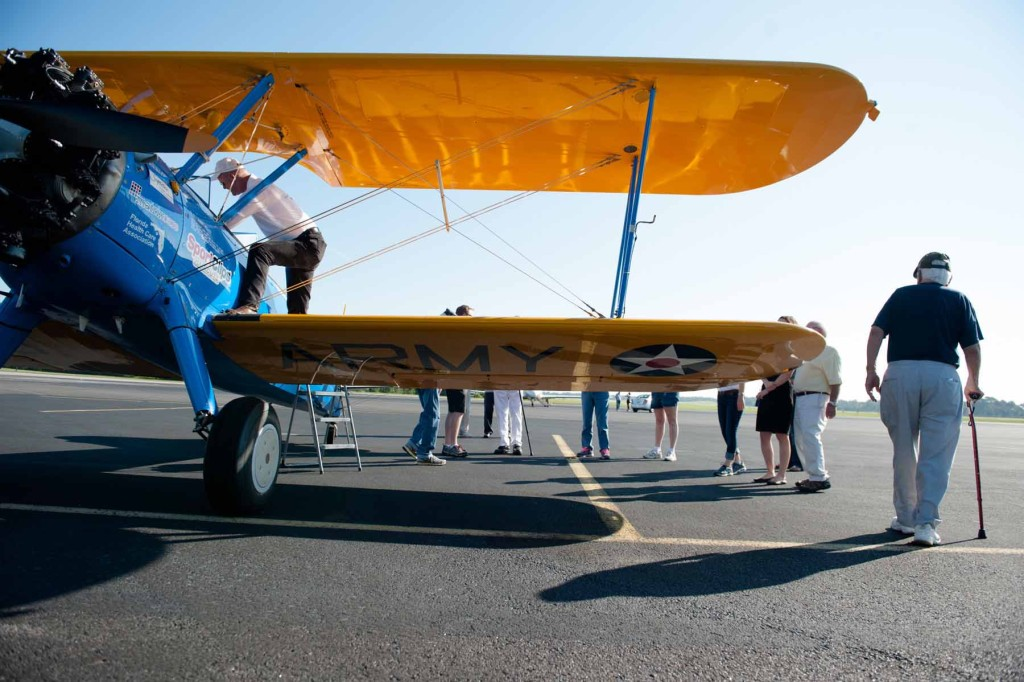 Members with the Southern Pines Gracious Retirement Living Community mingle on the tarmac as they prepare for their rides in Ageless Aviation's Pilot Darryl Fisher's Boeing Stearman biplane at the Moore County Airport on Tuesday, September 1, 2015 in Whispering Pines.