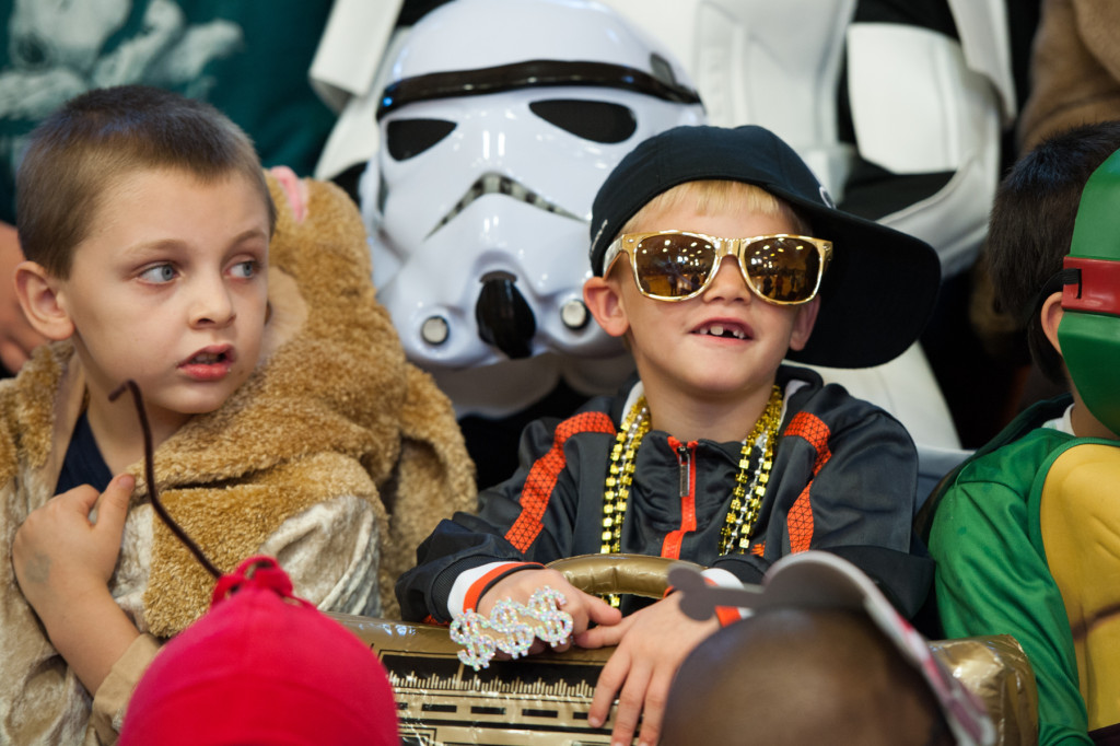 Chase Dunn (right) sits in the stands dressed up as a rapper with an inflatable boom-box as he and other students wait for the beginning of the Halloween Costume parade in the gymnasium of High Falls Elementary School on Friday, October 30, 2015 in Robbins, North Carolina.
