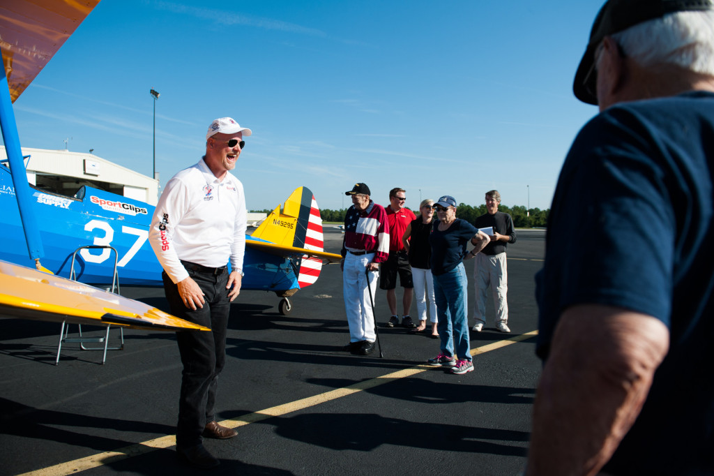 Founder, President and Pilot of Ageless Aviation Darryl Fisher laughs with the group of people from the Southern Pines Gracious Living Retirement Community before taking guests on rides in his Boeing Stearman biplane at the Moore County Airport on Tuesday, September 1, 2015 in Whispering Pines.
