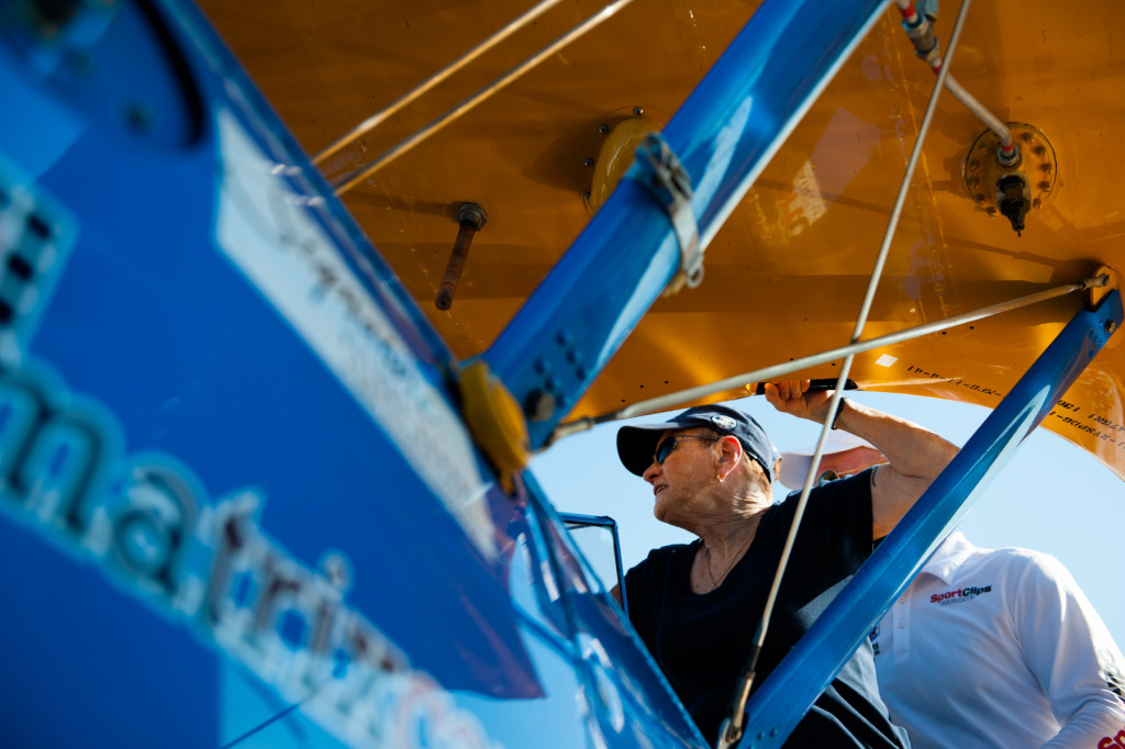 DeeDee Miller climbs into the co-pilot's seat at the front of Darryl Fisher's Boeing Stearman for her Ageless Aviation plane ride at the Moore County Airport on Tuesday, September 1, 2015 in Whispering Pines.