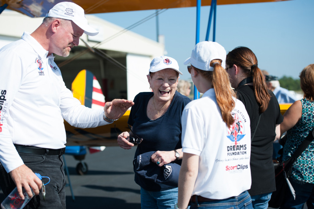 DeeDee Miller laughs with Founder, President and Pilot of Ageless Aviation Darryl Fisher and his daughter Nicole Fisher (far right) after Miller's plane ride at the Moore County Airport on Tuesday, September 1, 2015 in Whispering Pines.
