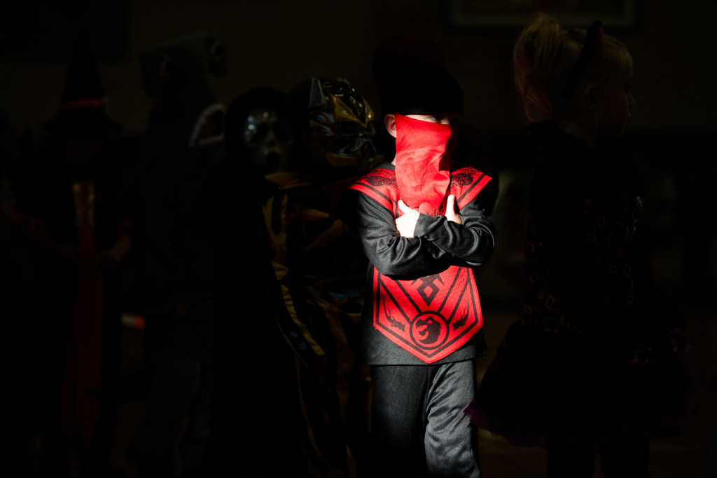 Bands of light stream across the students as they walk during the Halloween Costume parade in the gymnasium of High Falls Elementary School on Friday, October 30, 2015 in Robbins, North Carolina.