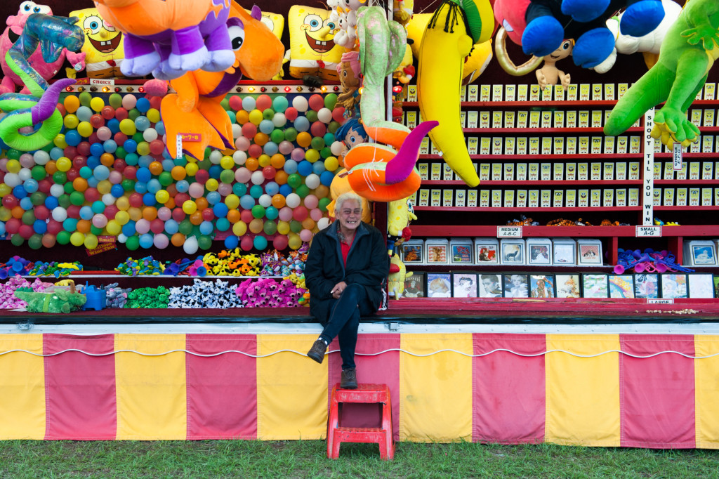 Game operator Jill sits at the Tag Balloon (left) and Quark Gun (right) booths as she waits for players at the Moore County Fair on Thursday, October 1, 2015 in Carthage, North Carolina.