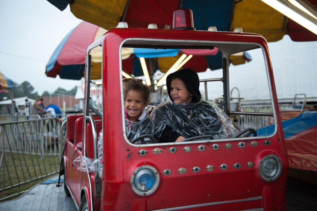 Three-year-old Jada Phillips (left) and 5-year-old Zeke Phillips (right) ride  in a fire-engine on a carousel  at the Moore County Fair on Thursday, October 1, 2015 in Carthage, North Carolina.