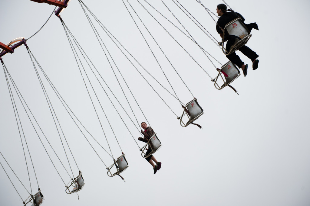 Two patrons ride the giant swing in the rain at the Moore County Fair on Thursday, October 1, 2015 in Carthage, North Carolina.