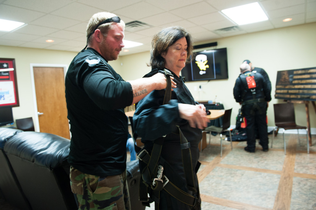 Tandem instructor Robbie Rushton helps Beth Patterson Casilio into her harness and gear as they prep for her tandem jump at the Raeford Drop Zone on Thursday, October 8, 2015 in Raeford, North Carolina.