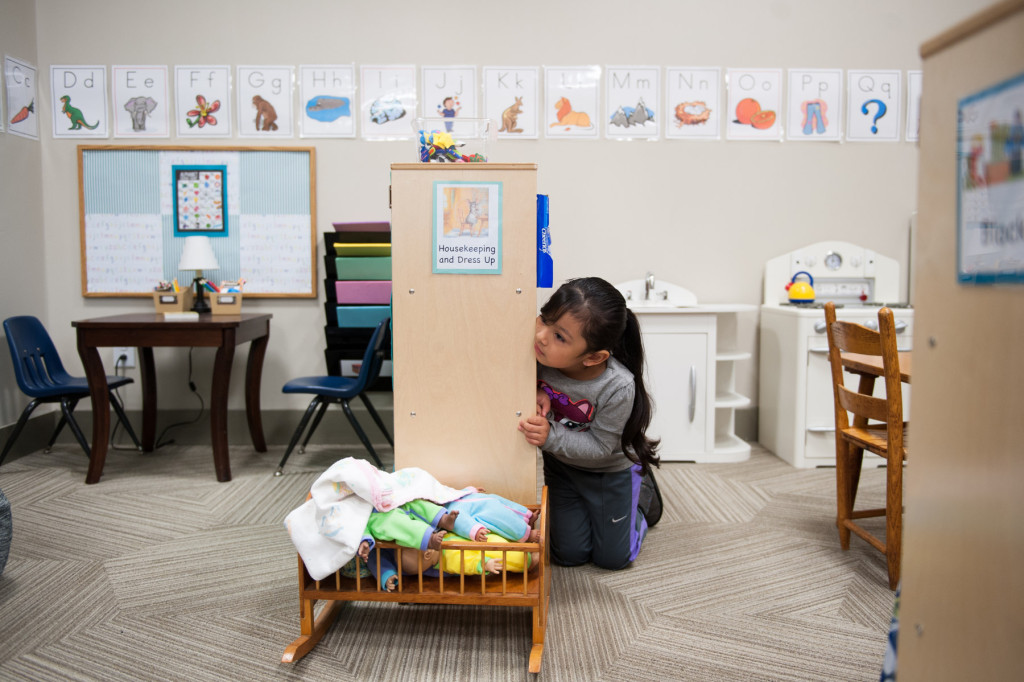 Jaidy Avila Parra peeks at her class during circle time in the toy kitchen area at HOPE Academy, a recently opened pre-school, on Wednesday, September 16, 2015 in Robbins, North Carolina.