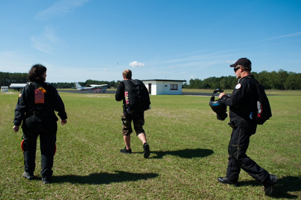 Tandem instructor Robbie Rushton (center) leads the group to their plane at the Raeford Drop Zone on Thursday, October 8, 2015 in Raeford, North Carolina.