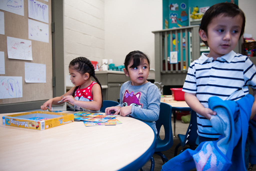 Julian Vargas takes off a sweater as Jaidy Avila Parra (center) and Hailey Prieto (left) play with puzzles at HOPE Academy, a recently opened pre-school, on Wednesday, September 16, 2015 in Robbins, North Carolina.