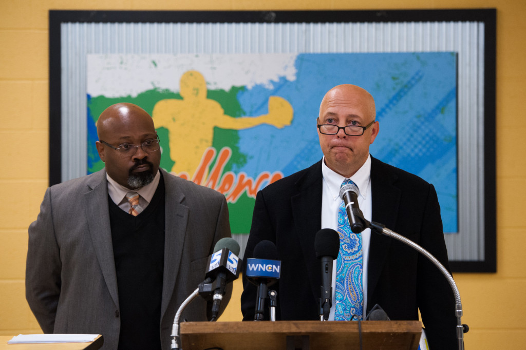 Principal Bob Christina speaks from behind a lectern, with Associate Superintendent of Secondary Education Eric Porter fielding questions from the media, about the violations ruled by the North Carolina High School Athletic Association concerning Pinecrest's football season in the cafeteria, during a press conference, at Pinecrest High School on Monday, November 9, 2015 in Southern Pines, North Carolina.