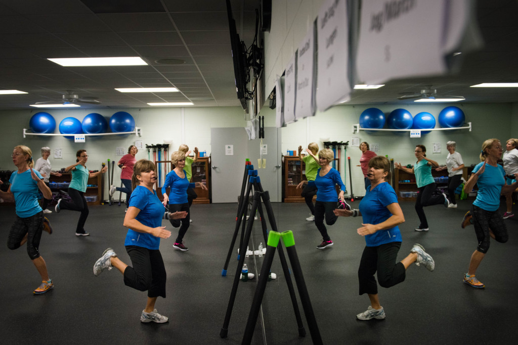 Esther Zollman (center, left) a fitness instructor, leads a Tabata class in the reflection of a large mirror in a work-out room at the Senior Enrichment Center on Monday, November 23, 2015 near West End, North Carolina. Tabata is a high-intensity work-out, followed with short rest periods.