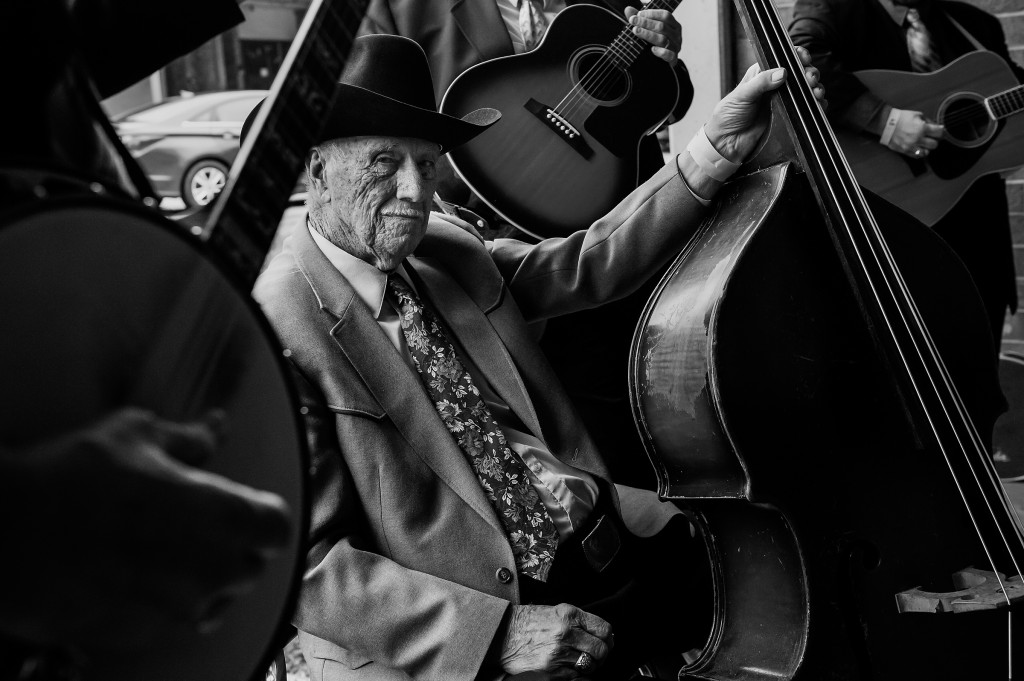 Ninety-year-old Theron Caviness sits with a bass as he waits outside of the auditorium before competing during the 80th Annual Fiddler's Convention at North Moore High School on Saturday, March 14, 2015 in Robbins, North Carolina.