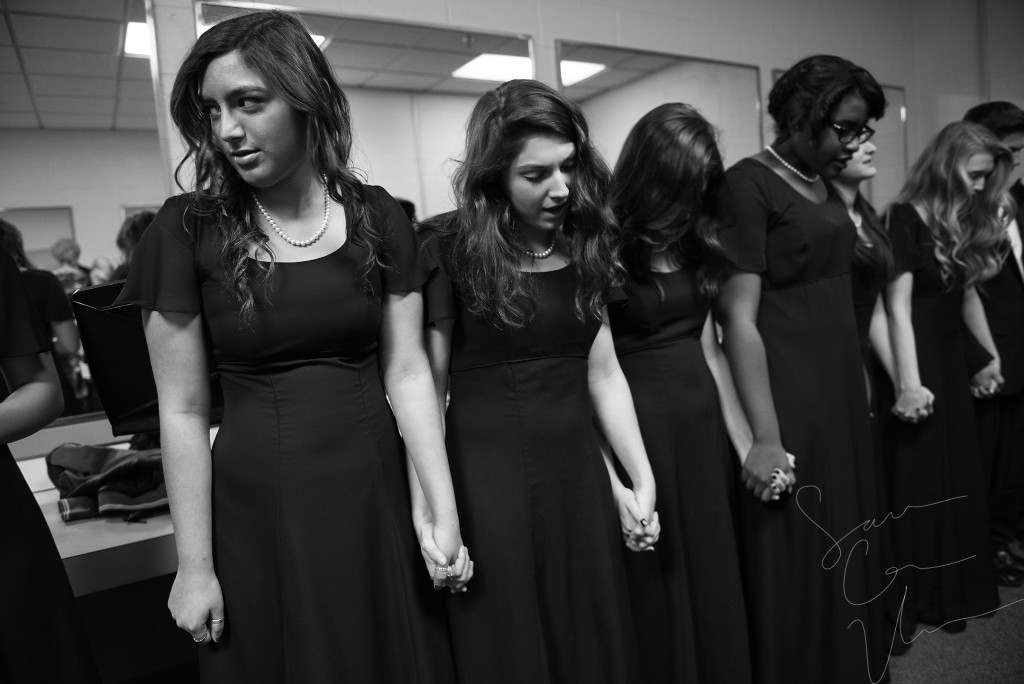 Sarah Tellez (left) and Madalyn Miller (center) hold hands with their fellow choir members as the group recites the Lord's Prayer backstage as they prepare to perform during the Holiday Concert in the Robert Lee Auditorium at Pinecrest High School on Saturday, December 12, 2015 in Southern Pines, North Carolina. The show was presented by the choral department featuring the Chamber Ensemble, Bella Voce, Concert Choir and the Holiday Madrigals.