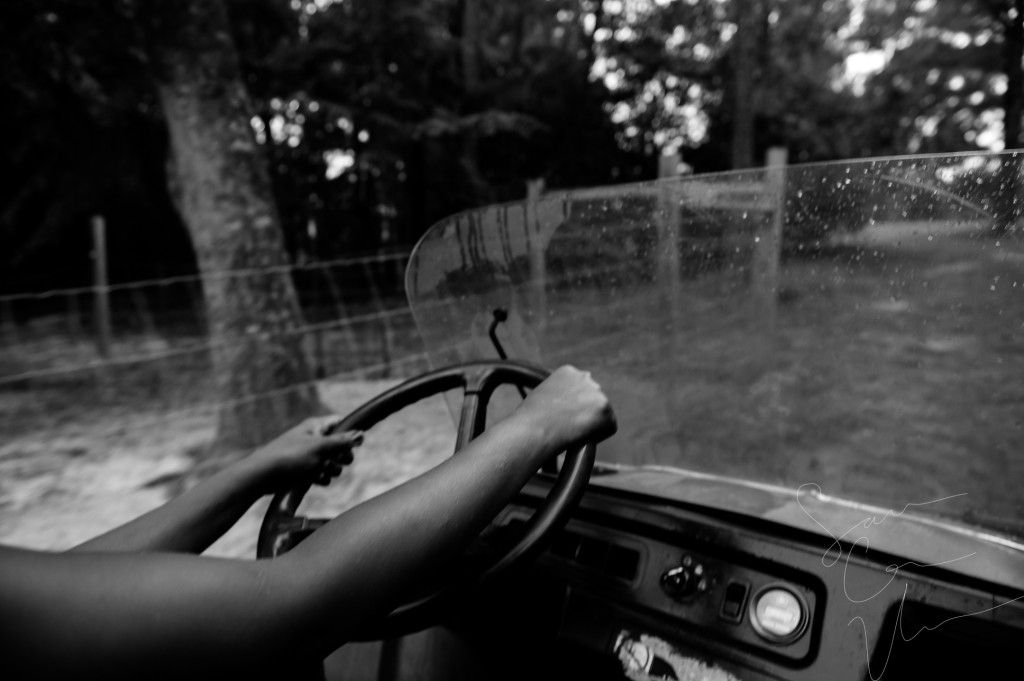 Volunteer Tema Toure drives a utility vehicle around the land on her morning feeding round at Paradox Farm on Tuesday, July 14, 2015 in West End, North Carolina.